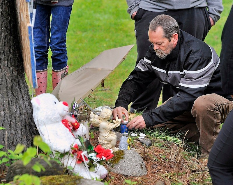 Timothy Munson, a neighbor and friend of Nichole Cable's family, relights candles Tuesday on the memorial for the 15-year-old at the base of the dirt road where she lived in Glenburn.