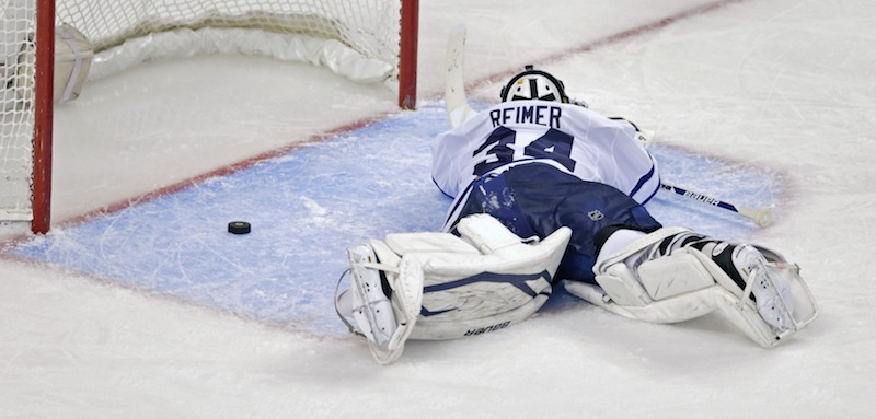Toronto Maple Leafs goalie James Reimer lays on the ice after getting beat on the game winning goal by Boston Bruins center Patrice Bergeron during overtime in Game 7 of their NHL hockey Stanley Cup playoff series in Boston, Monday, May 13, 2013. The Bruins won 5-4. (AP Photo/Charles Krupa)
