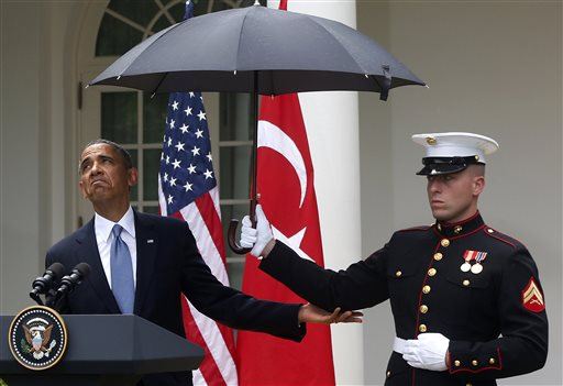 President Barack Obama looks to see if it is still raining as a Marine holds an umbrella for him during his joint news conference with Turkish Prime Minister Recep Tayyip Erdogan, not pictured, on Thursday at the White House.