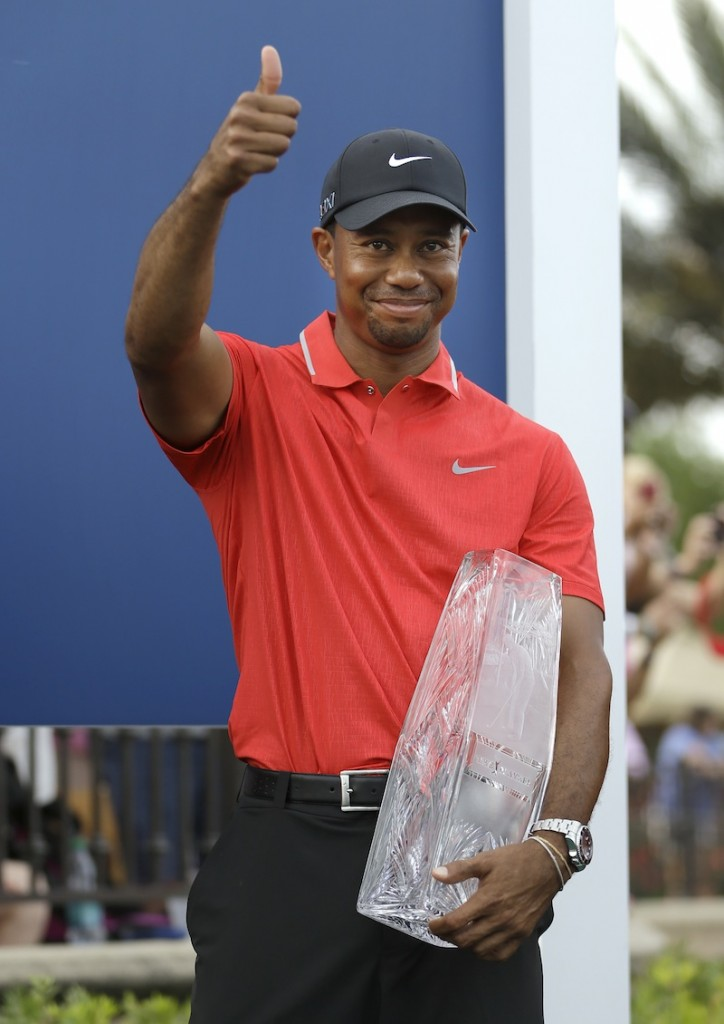 Tiger Woods gives a thumbs-up as he holds the trophy after winning The Players Championship golf tournament Sunday.