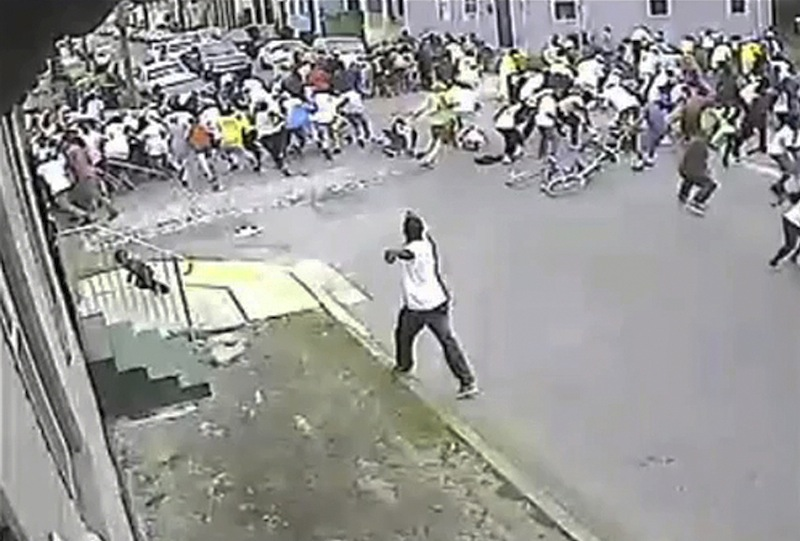 In this image taken from video and provided Monday, May 13, 2013, by the New Orleans Police Department, a possible shooting suspect in a white shirt, bottom center, shoots into a crowd of people, Sunday in New Orleans. The possible suspect may have two accomplices in the Mother's Day gunfire that wounded 19 people during a New Orleans neighborhood parade. (AP Photo/New Orleans Police Department)