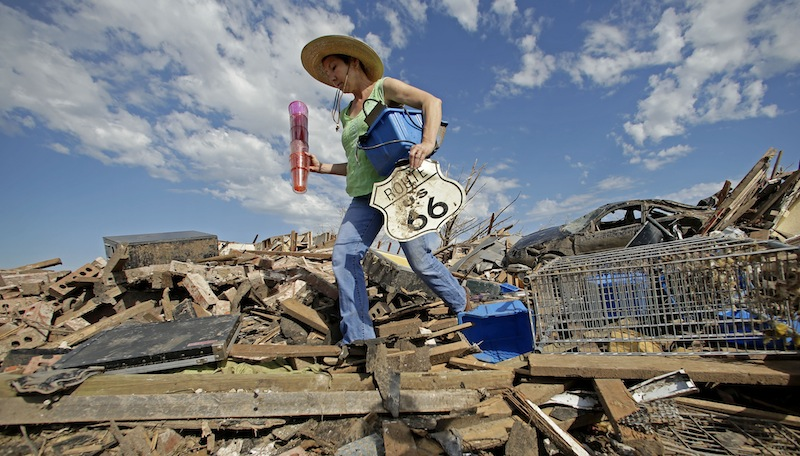 Susan Kates salvages items from a friend's tornado-ravaged home Wednesday, May 22, 2013, in Moore, Okla. Cleanup continues two days after a huge tornado roared through the Oklahoma City suburb, flattening a wide swath of homes and businesses. (AP Photo/Charlie Riedel)