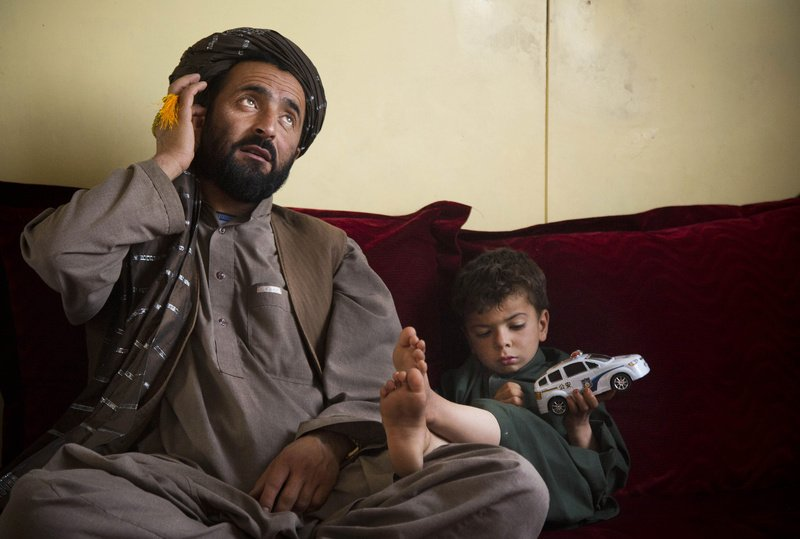 Mohammed Wazir sits with his only surviving son, Habib Shahin, 4, in Kandahar, Afghanistan, in April as he talks about the events of March 11, 2012, when a U.S. soldier burst into his family's home. Wazir returned to his home that morning to find 11 members of his family dead, their bodies partially burned. The youngest among the dead was his 1-year-old daughter Palawan Shah.