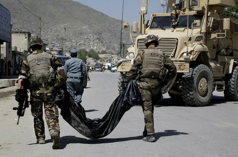 French soldiers with the NATO-led International Security Assistance Force, ISAF, carry the body of a victim killed from a suicide car bomber who attacked a NATO convoy in Kabul, Afghanistan, Thursday, May 16, 2013. A Muslim militant group, Hizb-e-Islami, claimed responsibility for the early morning attack, killing many in the explosion and wounding tens, police and hospital officials said. The powerful explosion rattled buildings on the other side of Kabul and sent a pillar of white smoke into the sky in the city's east. (AP Photo/Ahmad Nazar)