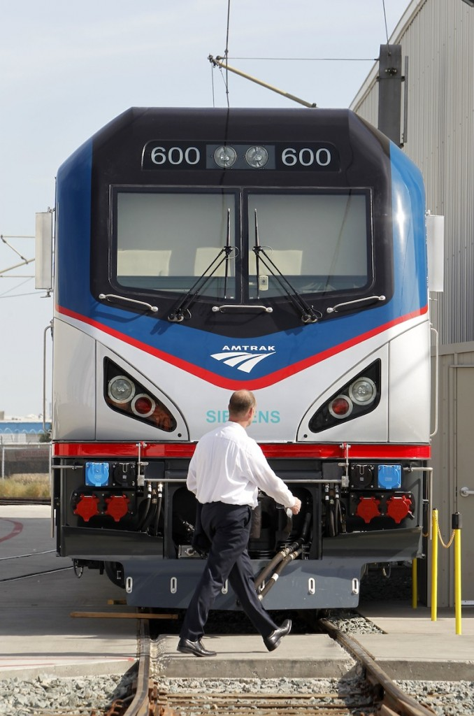 In this photo taken Saturday, May 11, 2013, Michael Cahill, president of Siemens Rail Systems, walks past one of the new Amtrak Cities Sprinter Locomotive that was built by Siemens in Sacramento, Calif. The new electric locomotive will run on the Northeast intercity rail lines and replace Amtrak locomotives that have been in service for 20 to 30 years.(AP Photo/Rich Pedroncelli)