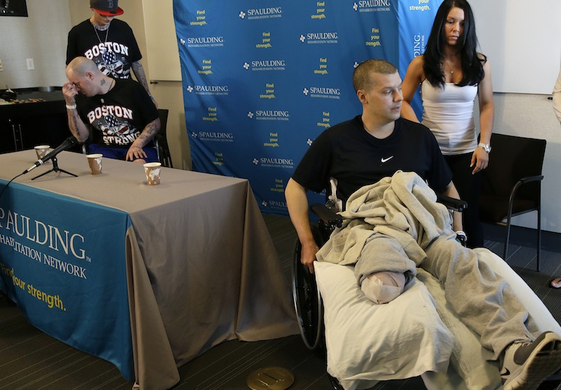 Paul Norden, left, and his brother J.P., right, both suffering limb-loss and major blast related injuries in the Boston Marathon bombing, prepare for a news conference at Spaulding Rehabilitation Hospital in Boston's Charlestown section Monday, May 13, 2013. Helping Paul at left is their younger brother, Jonathan, and at right is JP's girlfriend, Kelly Castine. (AP Photo/Elise Amendola)