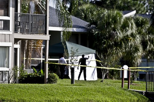 Investigators stand outside an apartment complex where a man was fatally by an FBI agent early Wednesday in Orlando, Fla.