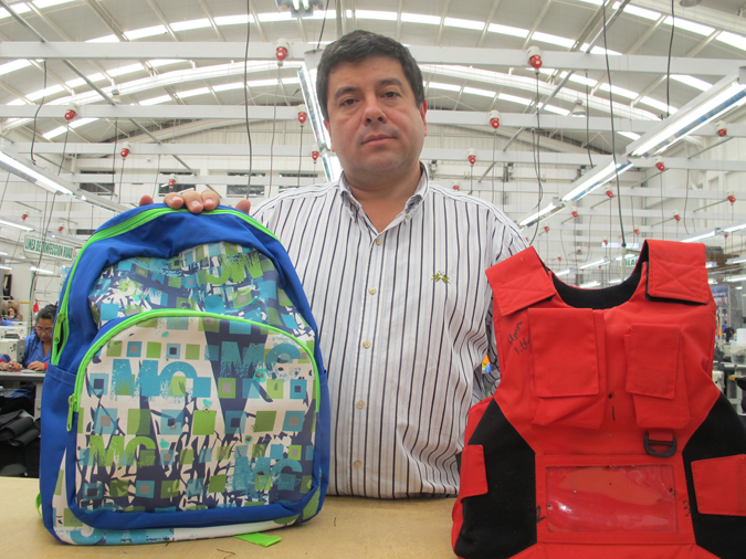 """Clothing maker Miguel Caballero, know as """"the Armani of bulletprooft clothing,"""" is shown at his factory in Bogota, Colombia, recently. He is holding two of his company's new products for American school children, a bulletproof backpack and vest."""