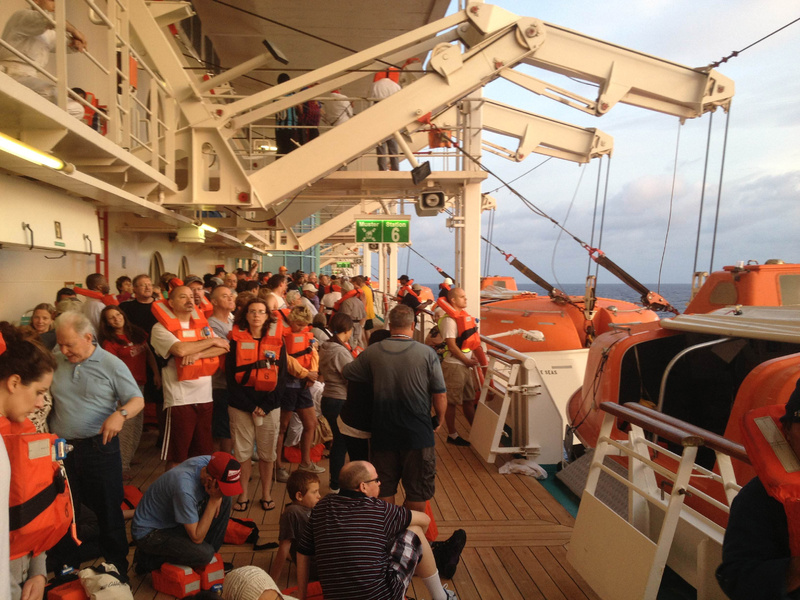 In this photo provided by passenger Marc Bell, passengers aboard the Royal Caribbean's Grandeur of the Seas cruise ship muster at sunrise Monday after a fire broke out during the ship's voyage from Baltimore to the Bahamas.