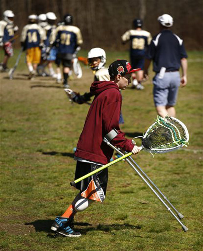 Matthew Freitas, 12, of Weymouth, Mass., makes his way across the lacrosse field where his school team is playing. He is helping to coach the team until he can play again.