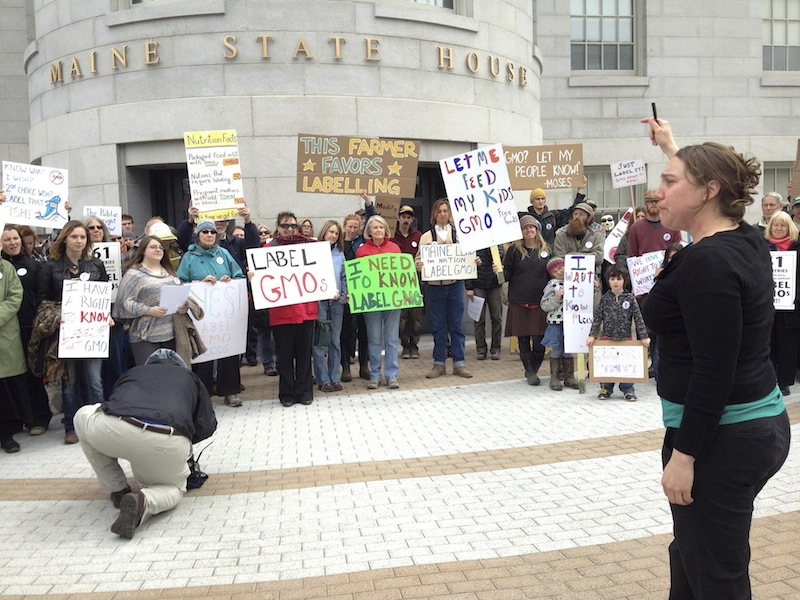 In this April 23, 2013 file photo, Logan Perkins of the Maine Organic Farmers and Gardeners Association, right, rallies supporters outside the State House for a bill that would require genetically modified products to be labeled. A legislative panel approved the bill 8-4 on Tuesday, May 14, 2013.