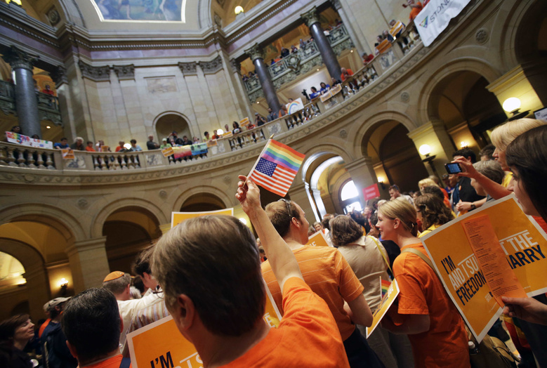 A gay marriage supporter waves the U.S. flag and a rainbow flag as supporters and opponents of Minnesota's gay marriage bill gather in the State Capitol rotunda in St. Paul on Monday in St. Paul, Minn.