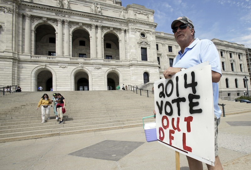 Mark Winiecki of Forest Lake, Minn., displays his opposition to Monday's passage of the gay marriage bill on the steps of the State Capitol Tuesday, May 14, 2013, in St. Paul, Minn. Gov. Mark Dayton will sign the bill, passed largely by the Democratic-Farmer-Labor (DFL) controlled Legislature, in front of the Capitol early Tuesday evening. (AP Photo/Jim Mone)
