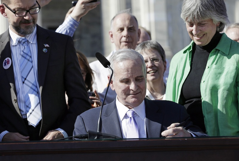Minnesota Gov. Mark Dayton signs the gay marriage bill in front of the State Capitol Tuesday, May 14, 2013, in St. Paul, Minn. Minnesota becomes the 12th state to legalize gay marriage. Looking over Dayton's shoulder are bill sponsors, Sen. Scott Dibble and Rep. Karen Clark. (AP Photo/Jim Mone)