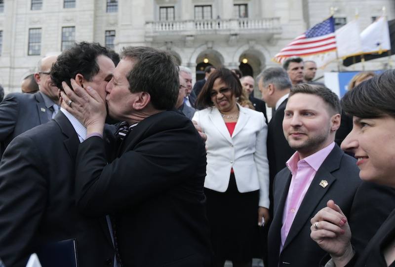 Rhode Island House Speaker Gordon Fox, left, is kissed by R.I. Rep. Frank Ferri, D-Warwick, after a gay marriage bill was signed into law outside the State House in Providence, R.I., Thursday, May 2, 2013. (AP Photo/Charles Krupa)