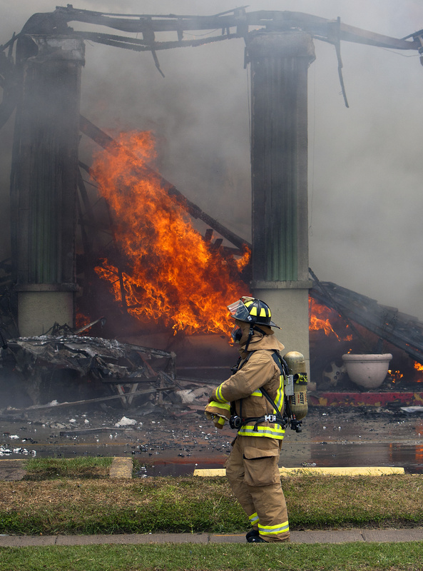 A firefighter stands near flames at the Southwest Inn on Friday in Houston.