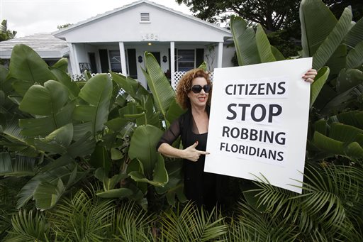Nancy Loft Powers poses with a sign she made in front of her home in Deerfield Beach, Fla., on Monday. Powers had to sell other properties she owned because she could no longer afford the insurance.