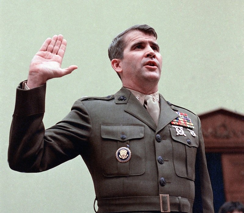 In this Dec. 18, 1986 file photo, Oliver North is sworn in on Capitol Hill in Washington prior to testifying before the House Foreign Affairs Committee. Lois Lerner of the IRS joins a diverse roll call of people who have invoked their Fifth Amendment right not to answer lawmakers' questions over the years. North cited his Fifth Amendment rights and refused to answer committee question availing the Iran arms sale. (AP Photo/J. Scott Applewhite, File) Arms Raised arms sales Iran Iran-Contra affair military Nicaragua Oath scandals