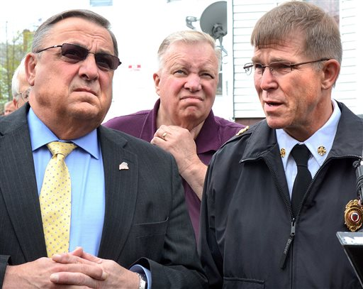 Gov. Paul LePage, left, and Lewiston Mayor Robert Macdonald, center, look up at two burned-out apartment buildings on Bartlett Street in Lewiston on Tuesday.