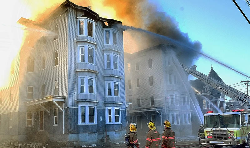 In this May 6 photo, firefighters battle the third major Lewiston fire in in a week, this one at 114-118 Bartlett Street. The four people accused of setting the three fires, which displaced about 200 residents, are due in Lewiston District Court today.