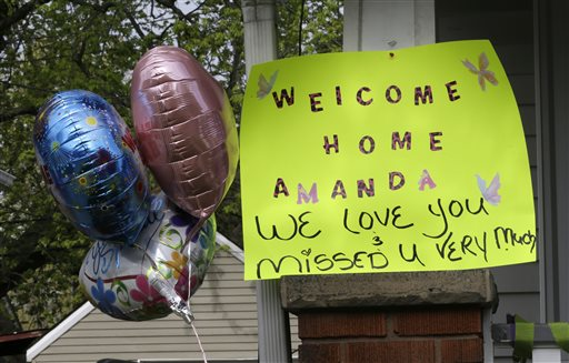 """A sign hangs on the porch of the home where Amanda Berry went on Wednesday. As word of Berry's homecoming spread, a large crowd swelled in the street outside the home decorated with dozens of balloons, and homemade signs, one reading """"We Never Lost Hope Mandy."""""""