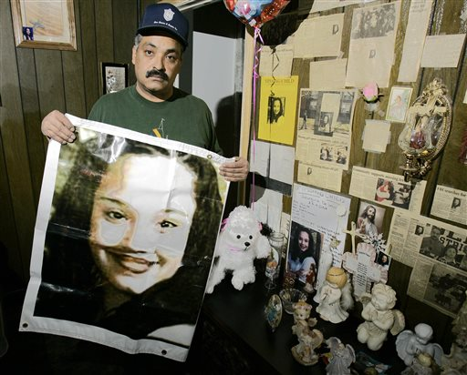 This 2004 file photos shows Felix DeJesus holding a banner showing his daughter's photograph. Gina DeJesus, Amanda Berry and Michele Knight were found Monday in a home near Cleveland.