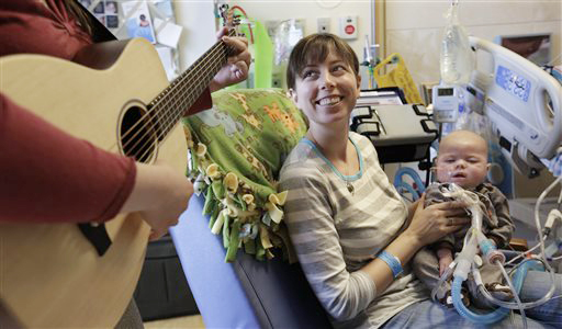 Music therapist Elizabeth Klinger, left, quietly plays guitar and sings for Henry Buchert and his mother Stacy Bjorkman, in the Pediatric Intensive Care unit at Ann & Robert H. Lurie Children's Hospital in Chicago.
