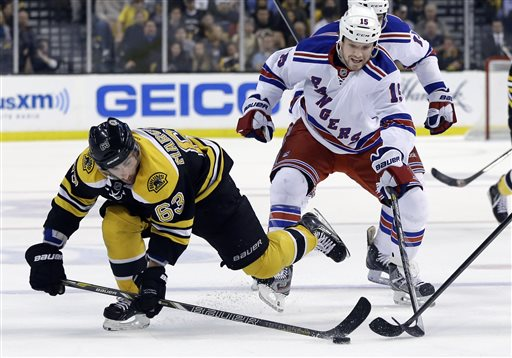 Boston Bruins left wing Brad Marchand gets to the puck ahead of New York Rangers right wing Derek Dorsett during Game 2 of the NHL Eastern Conference semifinal playoff series in Boston Sunday.