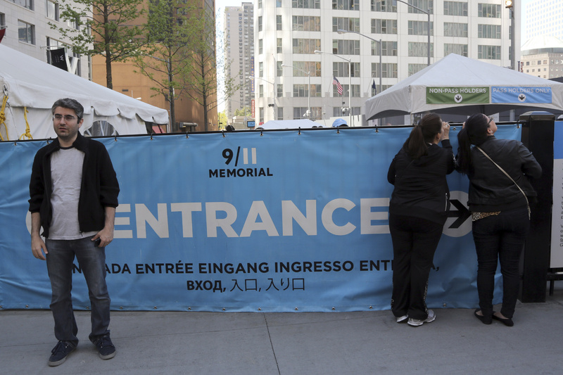 A visitor to the Sept. 11 Memorial poses for a photo as others peer at the entrance line Saturday in New York. Faced with hefty operating costs, the foundation building the underground 9/11 museum at the World Trade Center has decided to charge a mandatory admission fee of $20 to $25 when the site opens next year.