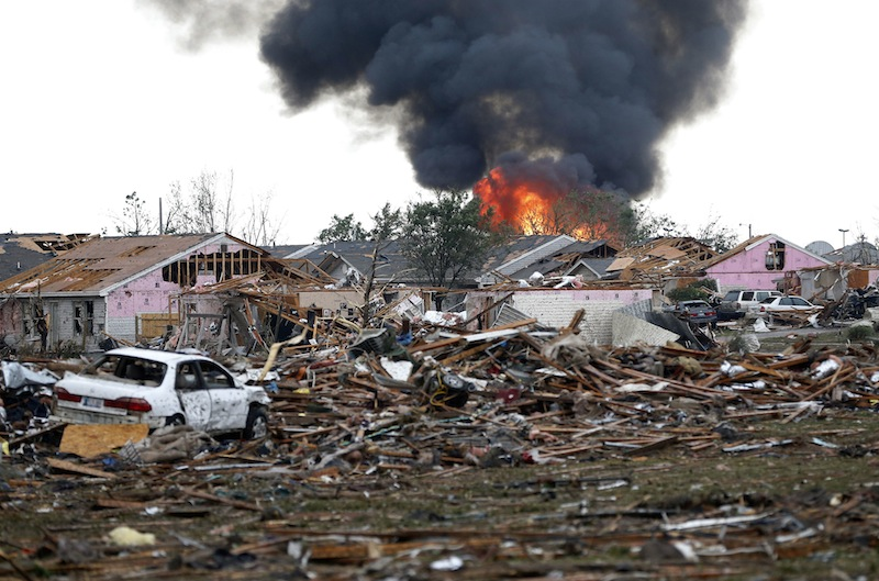 A fire burns in the Tower Plaza Addition in Moore, Okla., following a tornado Monday, May 20, 2013. A tornado as much as a mile wide with winds up to 200 mph roared through the Oklahoma City suburbs Monday, flattening entire neighborhoods, setting buildings on fire and landing a direct blow on an elementary school. (AP Photo Sue Ogrocki)