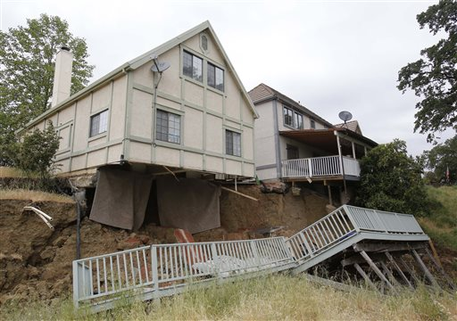 The bedroom carpets hang from the home of Jagtar Singh, left,on May 6 after the ground gave way in Lakeport, Calif. Shortly after Singh moved his wife, 4-year-old daughter and his parents to the subdivision, the hill behind his home collapsed taking the underside of his house.