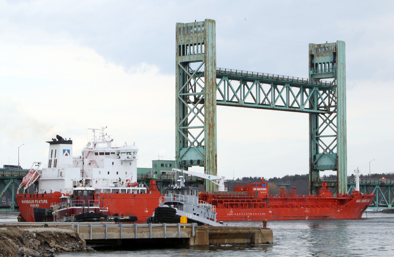 The 473-foot Harbour Feature rests against the Sarah Mildred Long Bridge on April 1 in Portsmouth, N.H. The estimate of the cost to repair the bridge has been lowered.