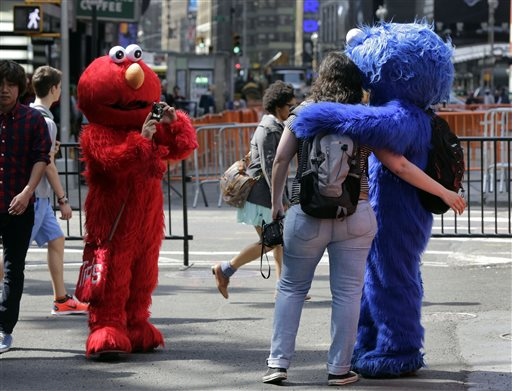 An Elmo character, left, uses a woman's camera to photograph her with a Cookie Monster character in New York's Times Square recently. A string of arrests in the last few months has brought unwelcome attention to the growing number of people, mostly poor immigrants, who make a living by donning character outfits, roaming Times Square and charging tourists a few dollars to pose with them in photos.