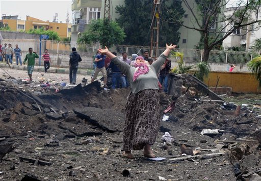 A woman cries at the scene of one of the explosion sites, after several explosions killed at least 18 people and injured dozens in Reyhanli, near Turkey's border with Syria, on Saturday, Turkish Interior Minister Muammer Guler said.