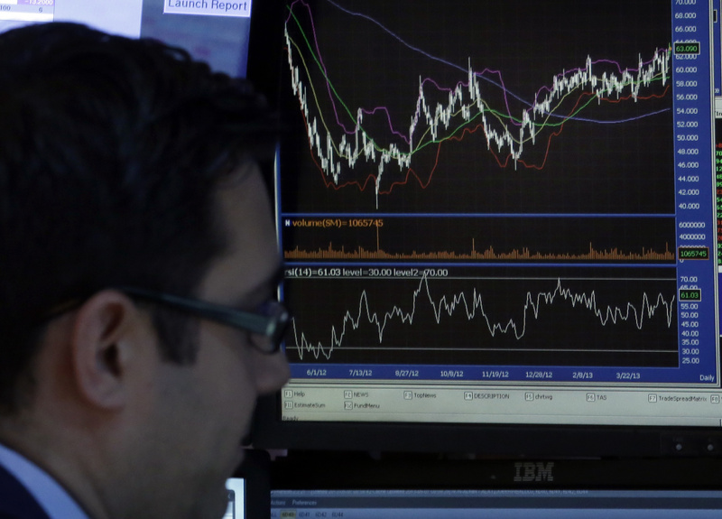 A specialist works at his post on the trading floor of the New York Stock Exchange on Tuesday. His screen shows the closing number for the Dow Jones industrial average, which topped 15,000 at the end of trading for the first time.