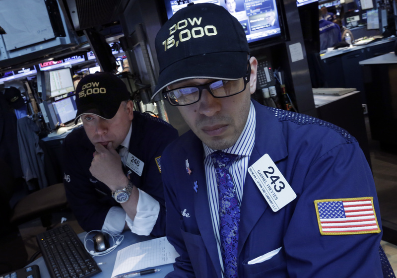 "Specialists Devin Cryan, left, and Gabriel Freytes wear ""Dow 15,000"" hats as they work on the floor of the New York Stock Exchange on Friday. The Dow Jones industrial average crossed 15,000 for the first time, and the Standard and Poor's 500 index, a broader market measure, rose above 1,600."