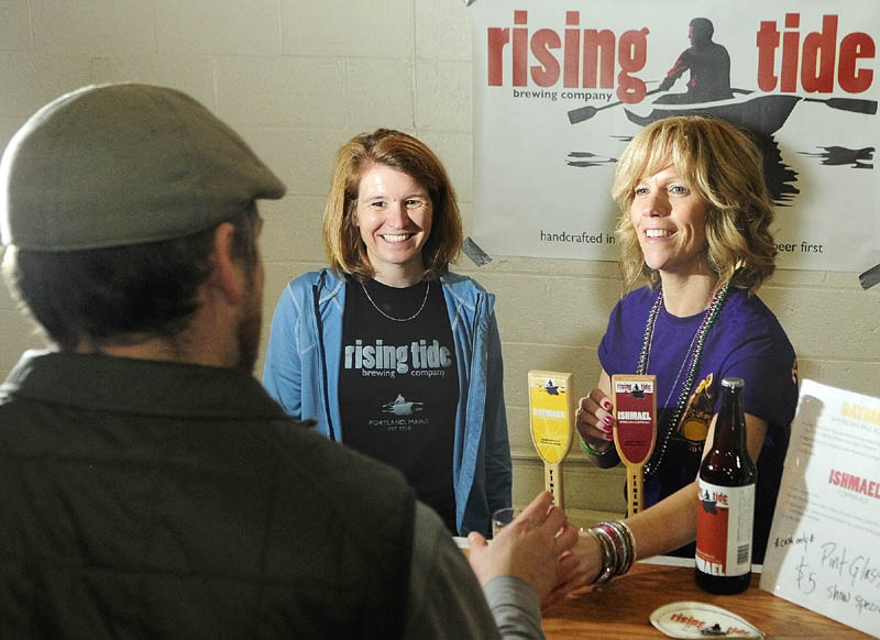 Brewery owner Heather Sanborn, left, and volunteer pourer Penny Vaillancourt talk to a customer at the Rising Tide booth at the Central Maine Brew Fest on April 13 in the Augusta Armory.