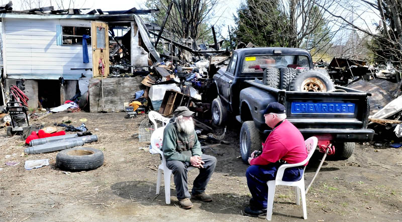 Home owner Clyde Berry, left, speaks with state Fire Marshall's Office investigator Ken MacMaster outside the ruins of his home in Benton that was destroyed by fire early Monday, April 29, 2013.