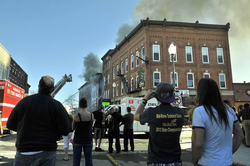 Crowds gather on Main Street in downtown Waterville on Friday afternoon as a building burns between Spring and Silver streets.
