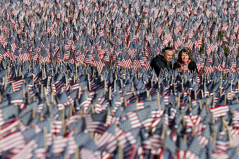 A couple photograph themselves amongst a sea of flags on Boston Common in Boston, Sunday, May 26, 2013. The flags were placed by the Massachusetts Military Heroes Fund in memory of every fallen Massachusetts service member from the Civil War to the present. (AP Photo/Michael Dwyer)