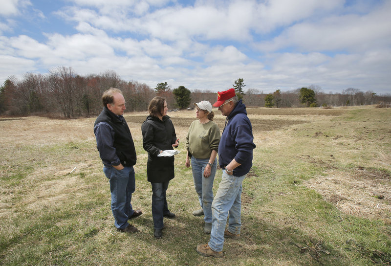 Tod Yankee, left, and Jamien Richardson talk with Kathy and Pete Karonis at the Karonises' Fairwinds Farm in Topsham. The farmers plan to sell some of their crops to Maine Harvest Co., a new enterprise being started by Richardson and Yankee in the former Navy Commissary in Topsham.