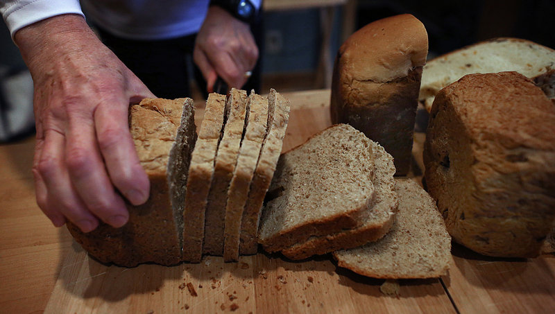 Dan Cole cuts bread into slices in preparation for serving.