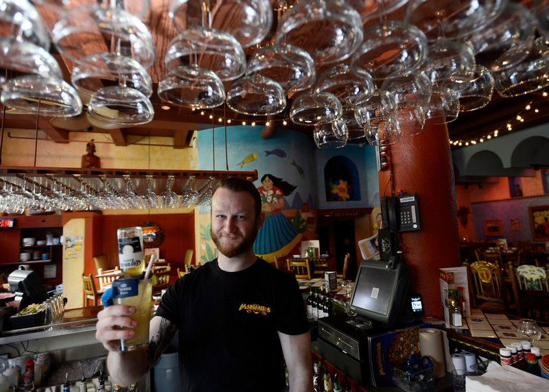 Jeff DiGiovanni, a bartender at Margaritas on Brown Street in Portland, presents a Coronarita, one of the more than a dozen types of margaritas the restaurant serves. Its happy hour specials include $1 baby chimis and $3 nachos.