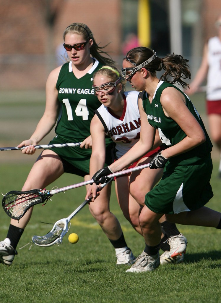 Emily Lewis of Gorham, center, competes for the ball with Sam Campobasso, left, and Shannon Sanborn of Bonny Eagle during Gorham's 12-5 victory Tuesday in a schoolgirl lacrosse game at Gorham.