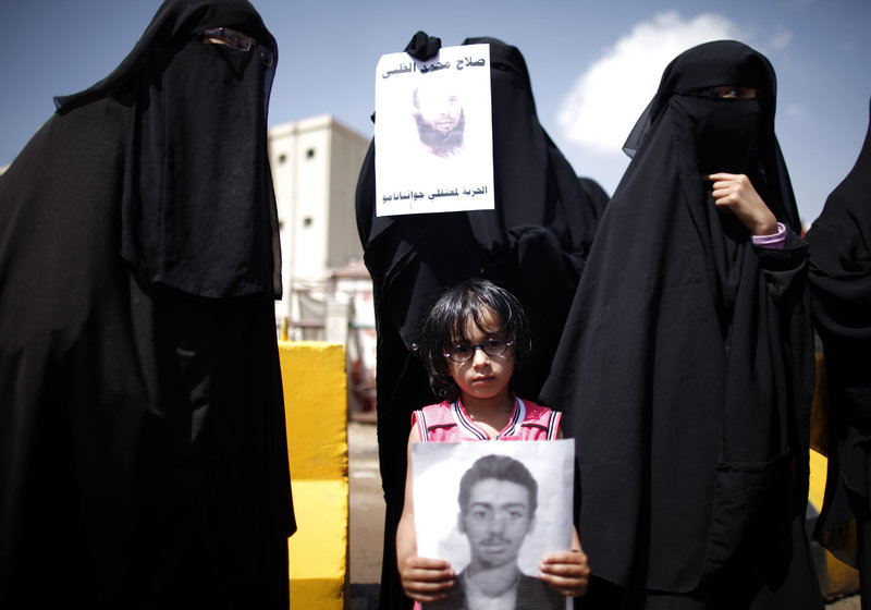 Faris al-Raimi, 5, holds a poster of his uncle during a protest to demand the release of Yemenis at Guantanamo Bay, Cuba, which holds 166 men captured in counterterrorism operations. Nearly all of them have been held for 11 years without charge.