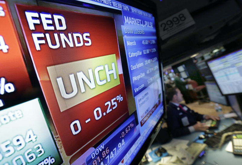 A New York Stock Exchange video screen displays the interest rate determined Wednesday by the Federal Reserve.