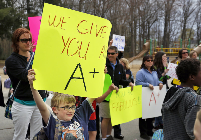 Harrison Greene, a student at the Fred P. Hall Elementary School, holds a sign in support of teachers at the school during a rally Thursday, May 2, 2013, to protest the grade of F given the school by the LePage administration.