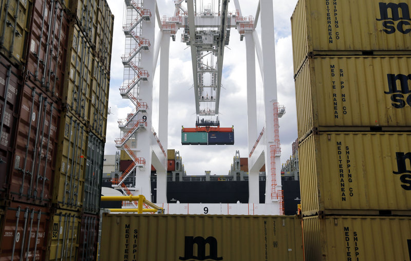 A crane removes a container from a ship at the Port of Baltimore's Seagirt Marine Terminal in March. The U.S. trade deficit narrowed in March for a second month.