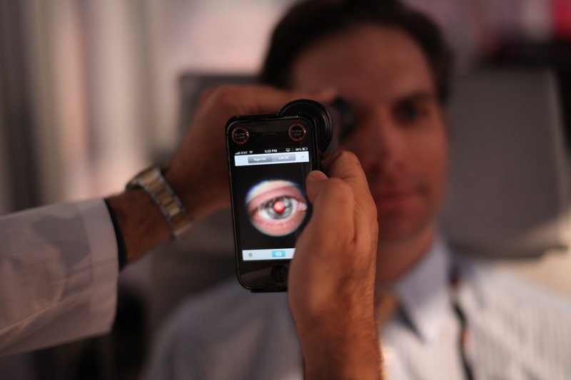 A medical student prepares to photograph the inside of an eye using a special tool that uses a smartphone camera during a recent TEDMED conference in Washington.