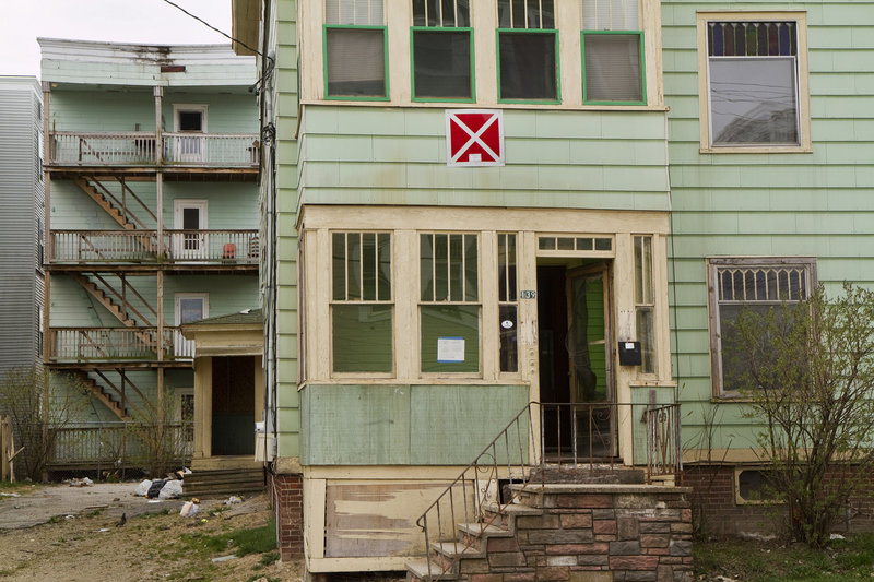 "The building at 139 Bartlett St. wears the signature red square with a white ""X,"" designating it as a condemned property."